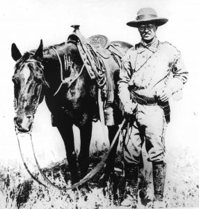 Theodore Roosevelt in Cowboy clothes with horse